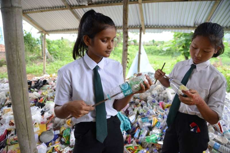 Indian students put plastic bags inside bottles to make eco-bricks, which will be used for construction purposes at the Akshar F