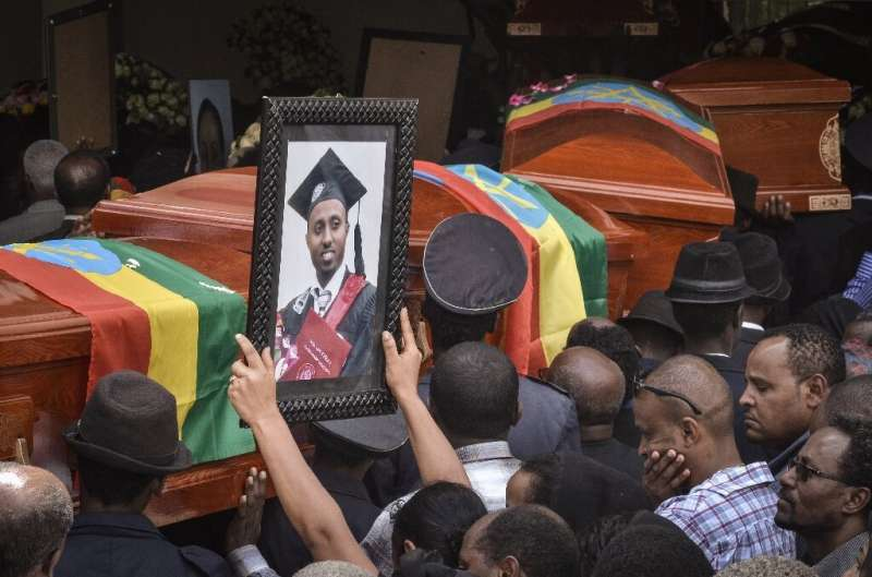 Mourners carry portraits of victims of the crashed accident of Ethiopian Airlines during a mass funeral at Holy Trinity Cathedra
