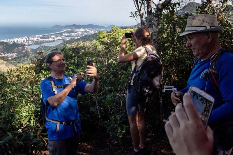 People take photos as they hike a trail above Rio de Janeiro, soon to be part of a countrywide network of hiking paths