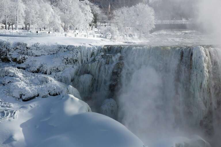 People walk in a park on the US side of Niagara Falls as seen from Niagara Falls, Ontario, Canada on January 31, 2019