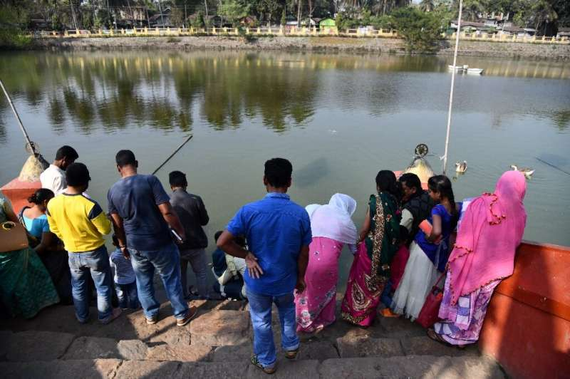Some of the hundreds of daily visitors to the temple feed bread to the turtles, which are losing their capacity to hunt