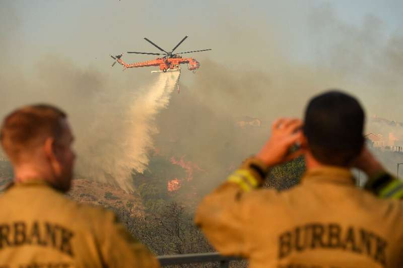 Firefighters watch a helicopter drop water on a burning hillside in Porter Ranch, California on October 11, 2019