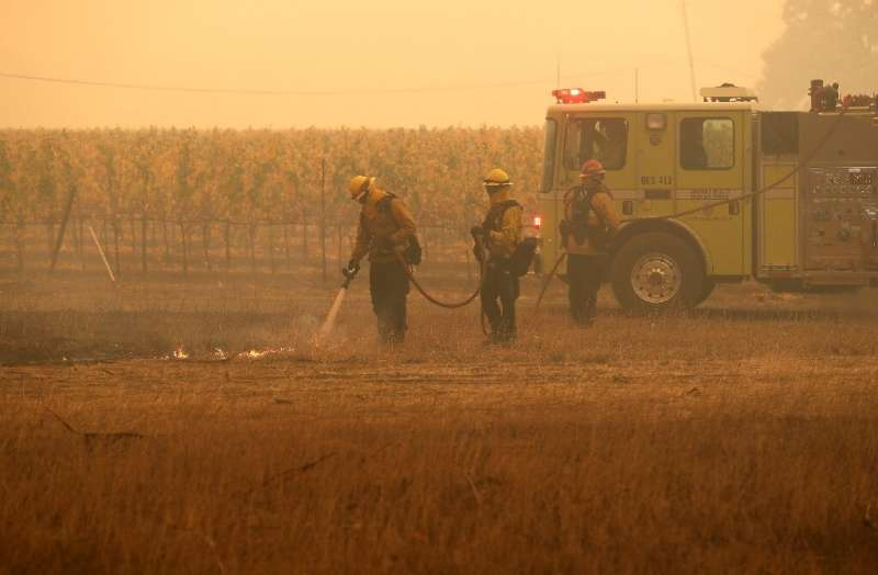 Firefighters put out a spot fire as they battle the Kincade Fire in Windsor, California
