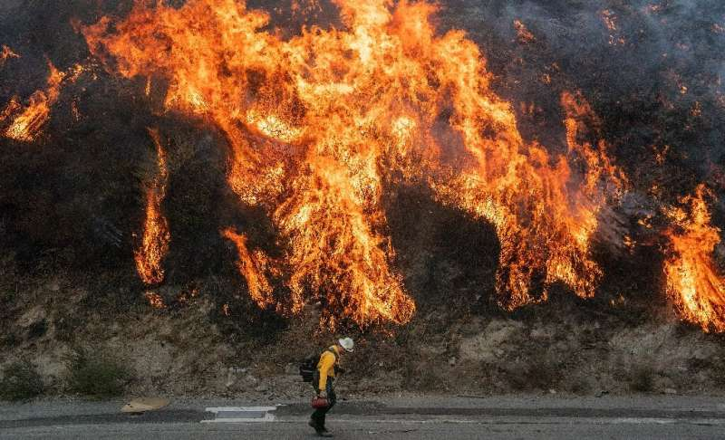 A firefighter walks near a backfire during the Saddleridge fire in Newhall, California on October 11
