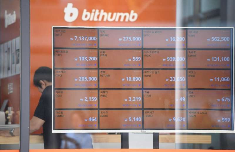 A man stands behind a screen showing exchange rates of cryptocurrencies at Bithumb virtual currency exchange in Seoul on June 20