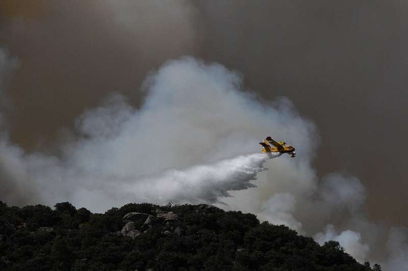 Firefighters in Spain battled high flames in strong winds and blistering heat just after they managed to contain another inferno