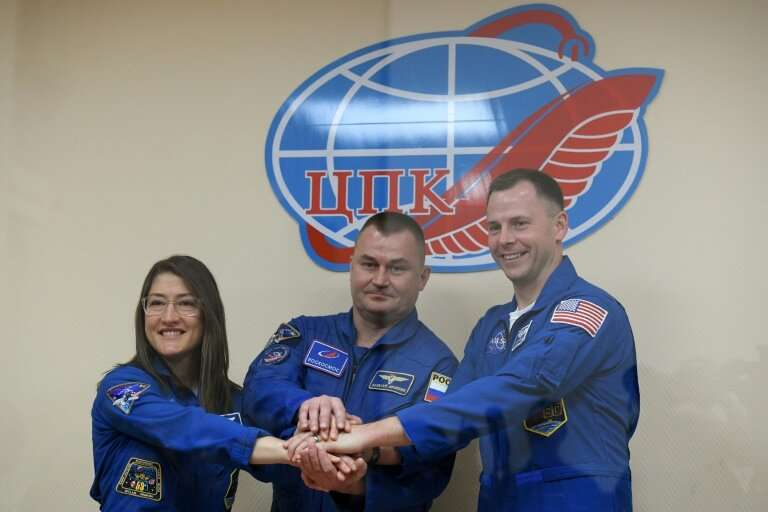US astronauts Christina Koch (L) and Nick Hague (R) together with Russian colleague Alexey Ovchinin blasted off on a mission to