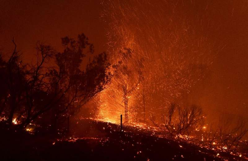 Wind blows embers as the Cave fire burns a hillside in Santa Barbara, California on November 26, 2019