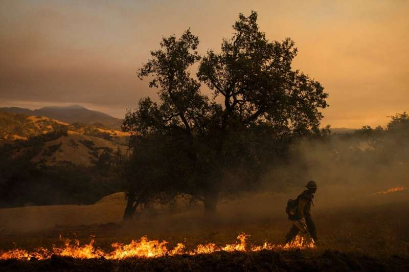 A firefighter sets a backfire along a hillside during operations to battle the Kincade Fire in Healdsburg, California on October