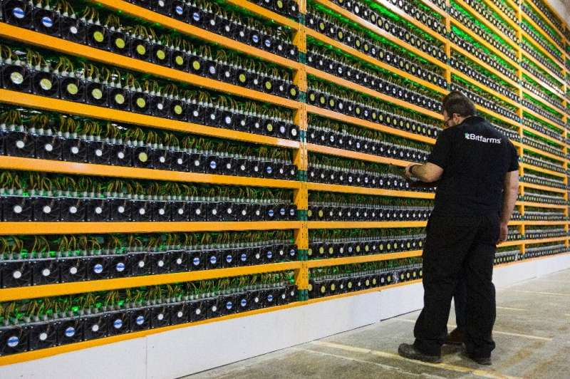 In this file photo taken on March 19, 2018 two technicians inspect bitcoin mining at Bitfarms in Saint Hyacinthe, Quebec