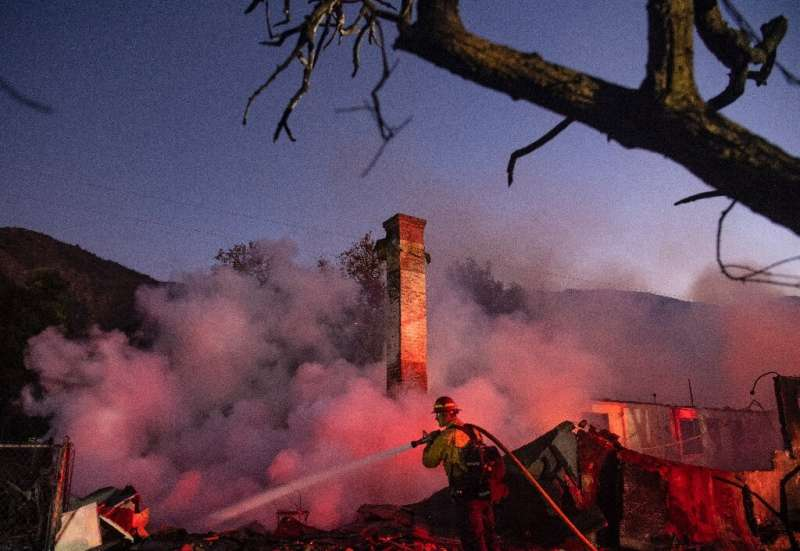 A firefighter douses a smoldering home during the Hillside Fire in the North Park neighborhood of San Bernardino, California on
