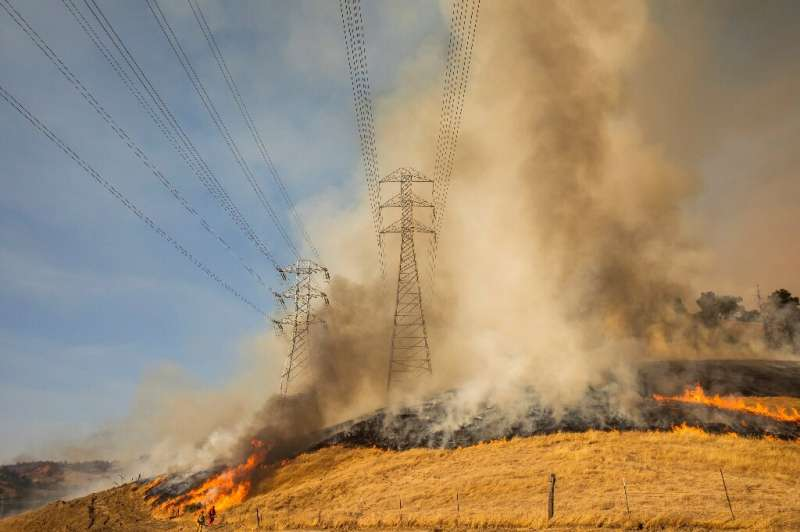 A backfire set by firefighters burns a hillside near PG&E power lines during operations to battle the Kincade Fire in Healds