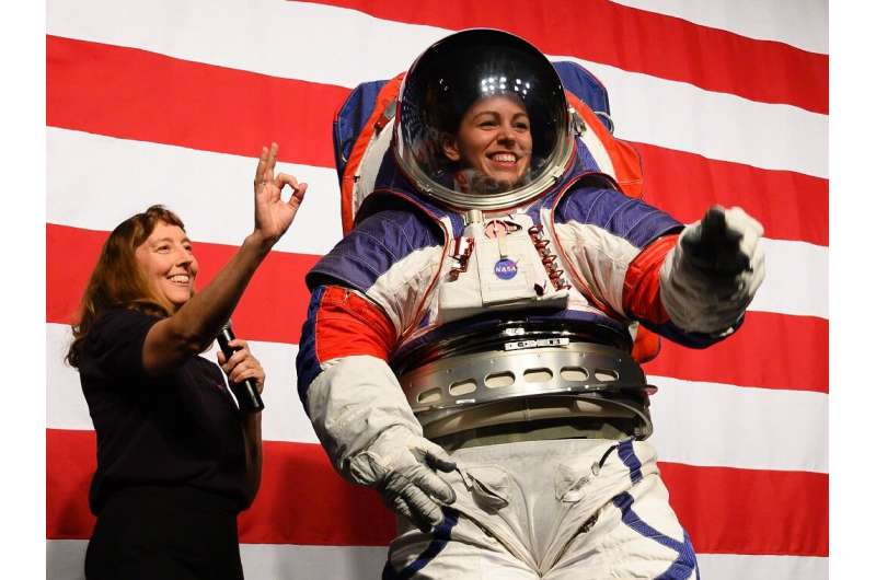Advance space suit engineer, Kristine Davis (R), waves next to space suit engineer Amy Ross (L) during a press conference displa