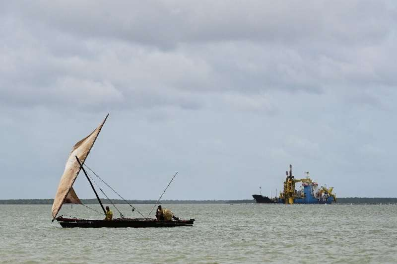A fishing dhow sails past a dredger, digging out the sea floor near a planned port in Lamu