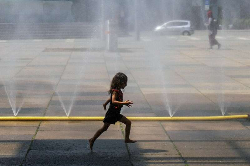 A girl runs through water at Praterstern Square in Vienna on July 25 amid a blistering heat wave