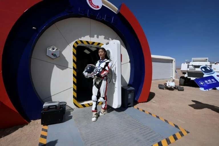 """A guide wearing a space suit stands at an entrance to """"Mars Base 1"""" in the Gobi desert in China"""