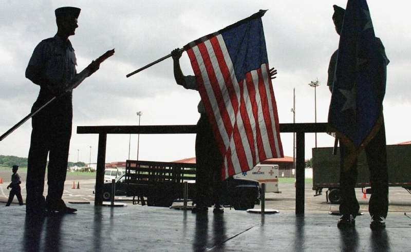 Air Force personnel fold a US flag as they prepare to leave the Howard Air Force Base in the Panama Canal Zone in June 1999