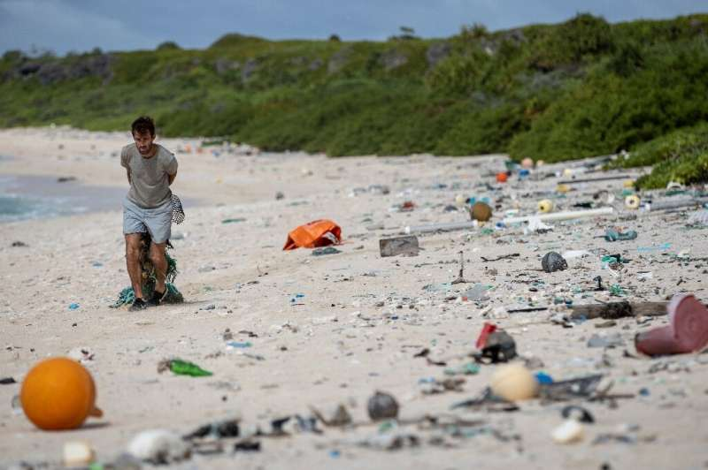 A man cleans up the beach on  Henderson Island in the Pacific in June 2019