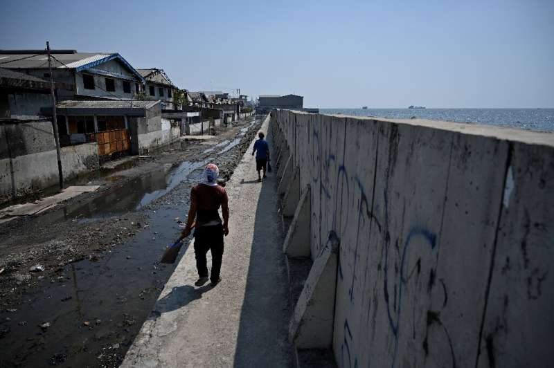 A man walks on a giant sea wall to avoid a flooded road next to abandoned warehouses in northern Jakarta
