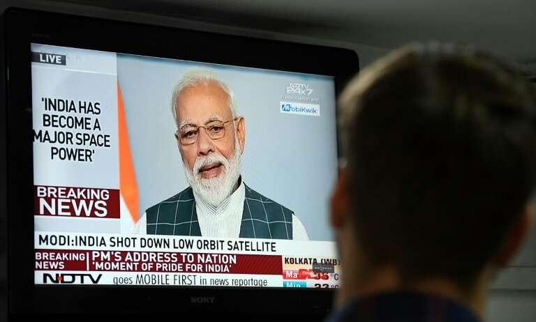 A man watches Indian Prime Minister Narendra Modi's address to the nation on a local news channel declaring his country is a spa