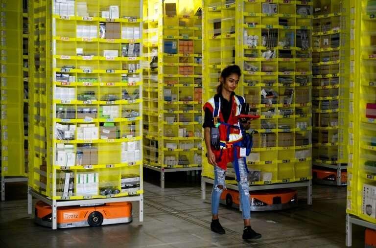 Amazon employee Deasahni Bernard moves among robots at the 855,000-square-foot Amazon fulfillment center in Staten Island Februa