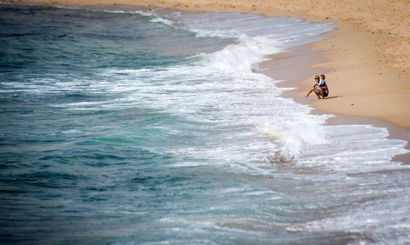 A Moroccan man carries a child on a beach in the Moroccan city of Mohammedia