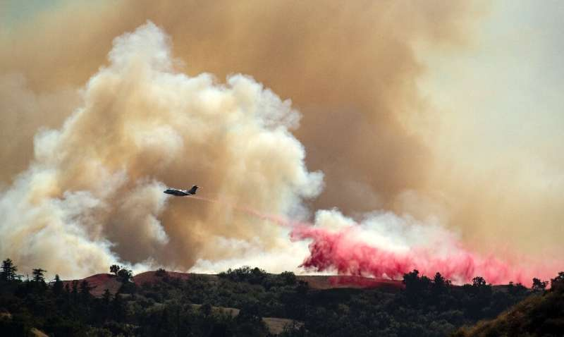 An aircraft helps fight the Saddleridge fire, dropping fire retardant along a ridge in Newhall, California on October 11