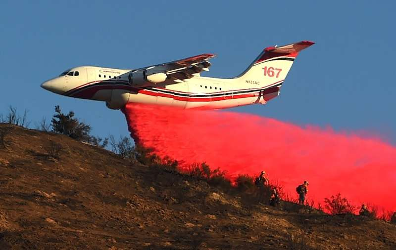 An air tanker drops fire retardant over power lines while helping to fight the Hillside Fire in the North Park neighborhood of S