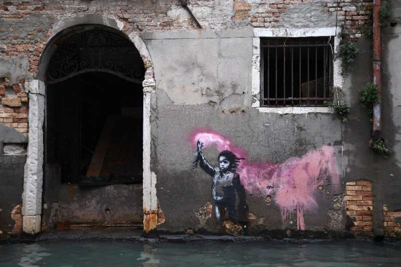 An artwork by Banksy portraying a migrant child wearing a lifejacket and holding a neon pink flare remained just above water dur
