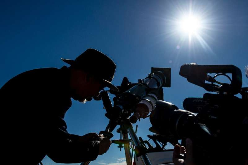 An astronomer looks at the sun through a telescope on the eve of a solar eclipse at La Higuera in Chile's Coquimbo Region on Jul