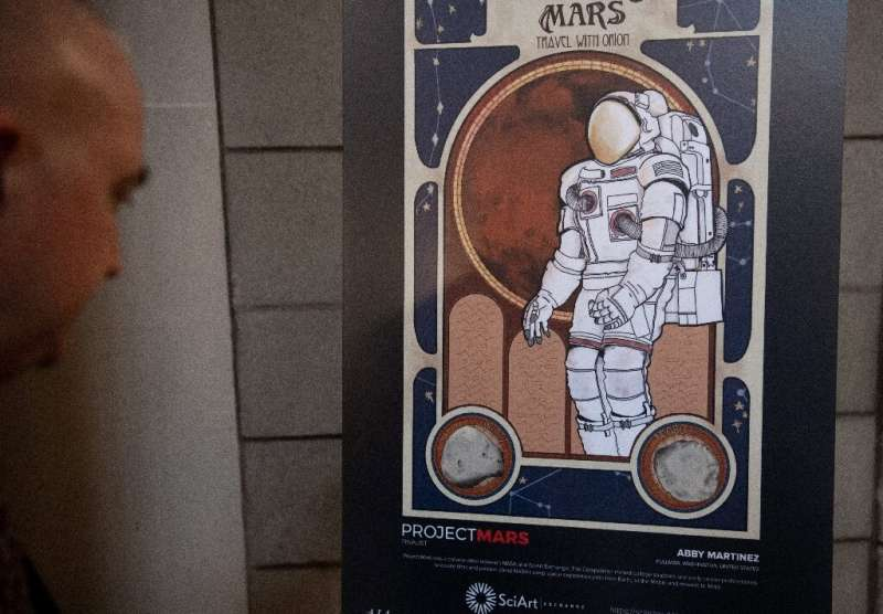 An attendee looks at a poster during the Humans to Mars Summit, which aims to advance humanity to the Martian surface by the 203