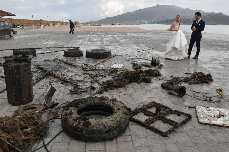A newly-wed couple looks at the rubbish collected from the sea by volunteers from Aegean Rebreath