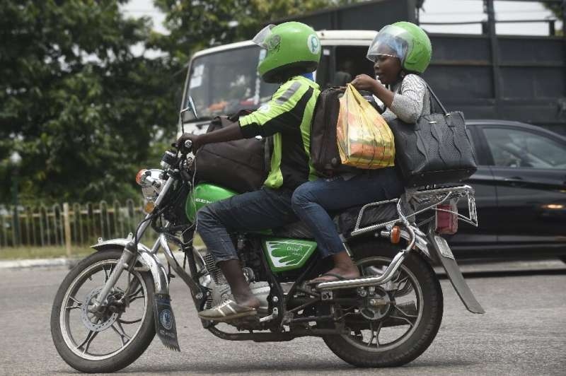 An ORide driver, decked out in bib and helmet, takes a passenger through the Lagos gridlock