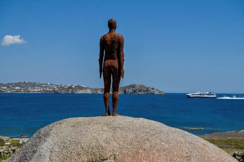 'Another time XV', by Antony Gormley, standing at the entrance to the small island of Delos, looking across to Mykonos