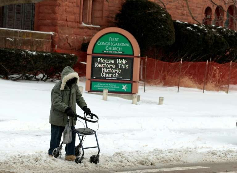A person with a walker crosses Canfield Avenue in Detroit, Michigan