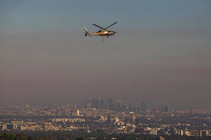 A rescue helicopter flies over Brentwood while the Los Angeles skyline is seen behind smoke from the Getty Fire