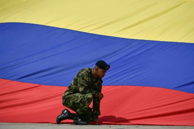 A soldier holds down a Colombian flag; the biodiverse South American nation has moved to ban hunting for sport
