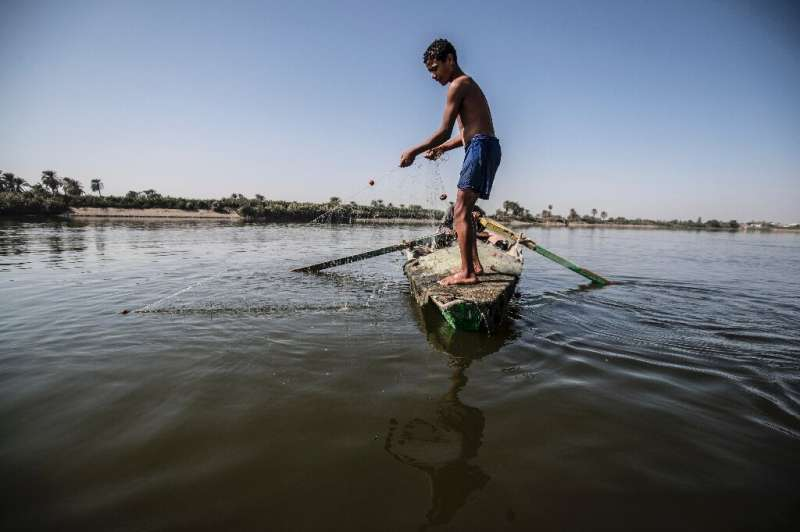 A young Egyptian fisherman pulls his net in the River Nile, south of the Egyptian capital, with Egypt suffering for years from a