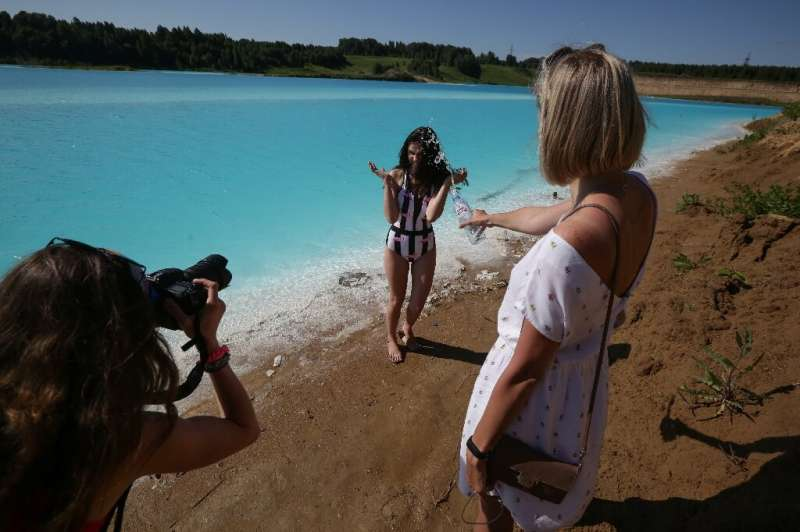 """A young woman poses for pictures by the ash dump site—nicknamed the local """"Maldives""""—but what appears a tropical parad"""