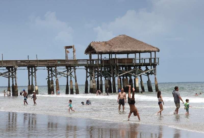 Beach-goers play in the surf near the Cocoa Beach Pier ahead of the arrival of Hurricane Dorian