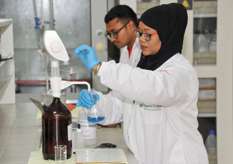 Chemists work in a laboratory at a desalination plant in the Omani port city of Sur, south of the capital Muscat