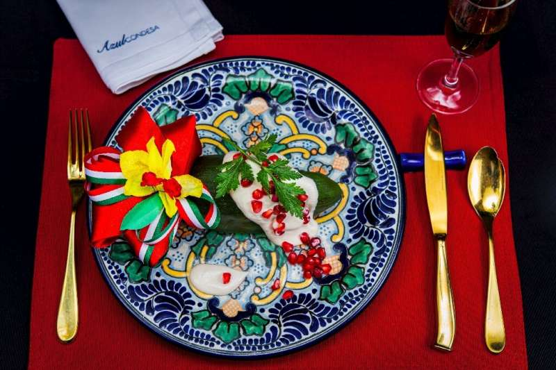 Chile en Nogada, an iconic Mexican dish featuring poblano chile peppers bathed in creamy white sauce and topped with red pomegra
