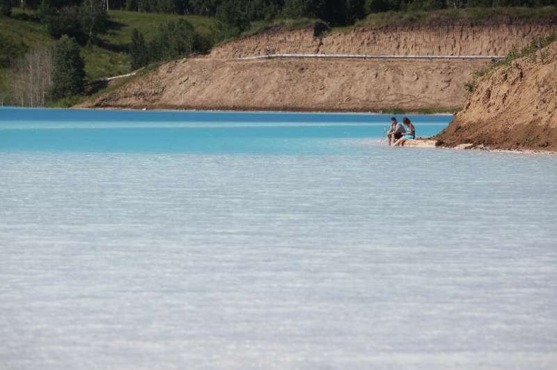 """Despite """"Danger Zone"""" signs, a couple risk cooling their feet at the edge of the turquoise lake—but the Siberian Gener"""