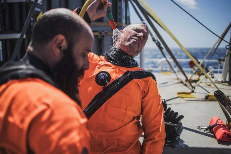 Divers rinse themselves with clean water after a dive to the seamount