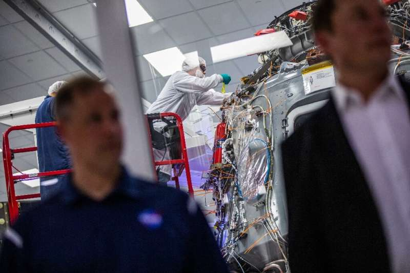 Employees of SpaceX work on the Crew Dragon reusable spacecraft during a press conference at SpaceX headquarters in Hawthorne, C