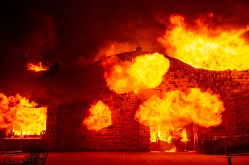 Fire explodes out the entrance of the Soda Rock Winery as it burns during the Kincade fire