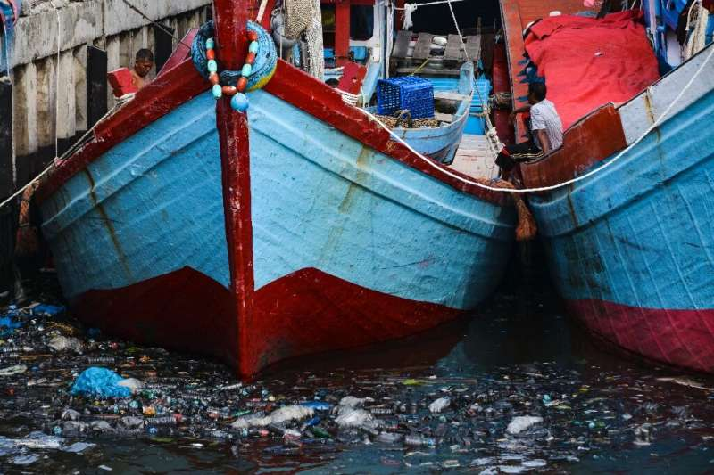 Fishing boats sit in trash-filled waters in Banda Aceh, Indonesia on July 16, 2019