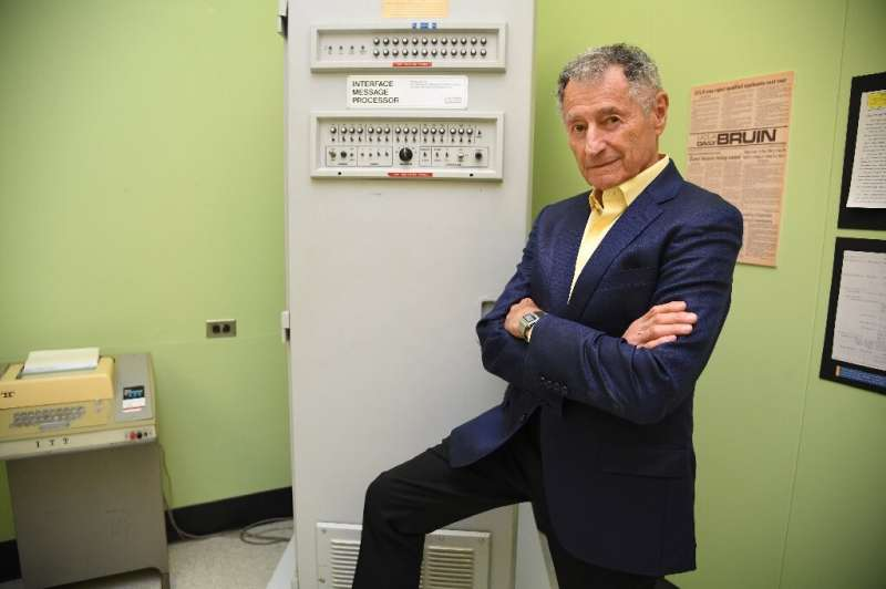 Leonard Kleinrock poses beside the first Interface Message Processor (IMP) in the lab where the first internet message was sent,