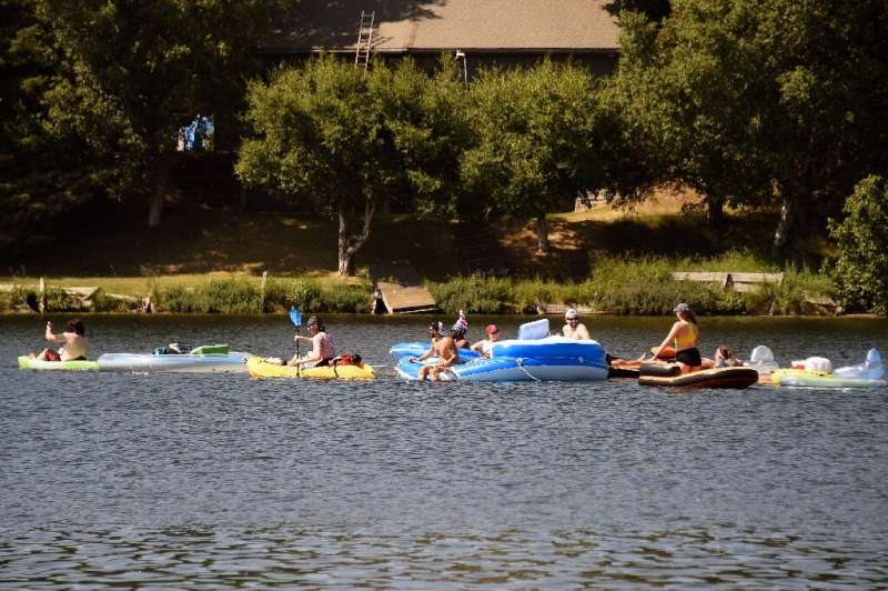 Lightly clad Alaskans take advantage of a record heat wave to enjoy lake fun in the city of Anchorage on July 4, 2019