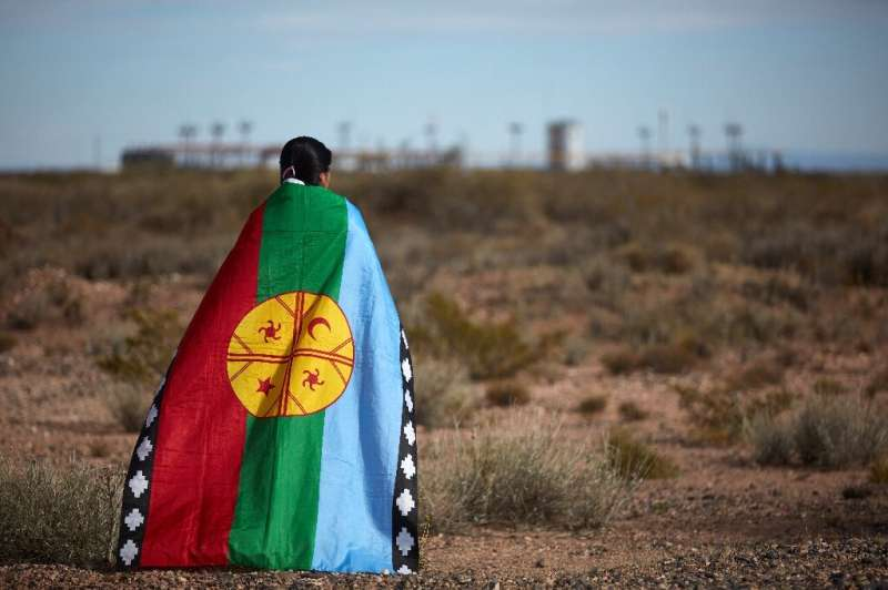 Mapuche indigenous spokeswoman Lorena Bravo stands wrapped in a Mapuche flag near a gas plant at Campo Maripe, on land claimed b